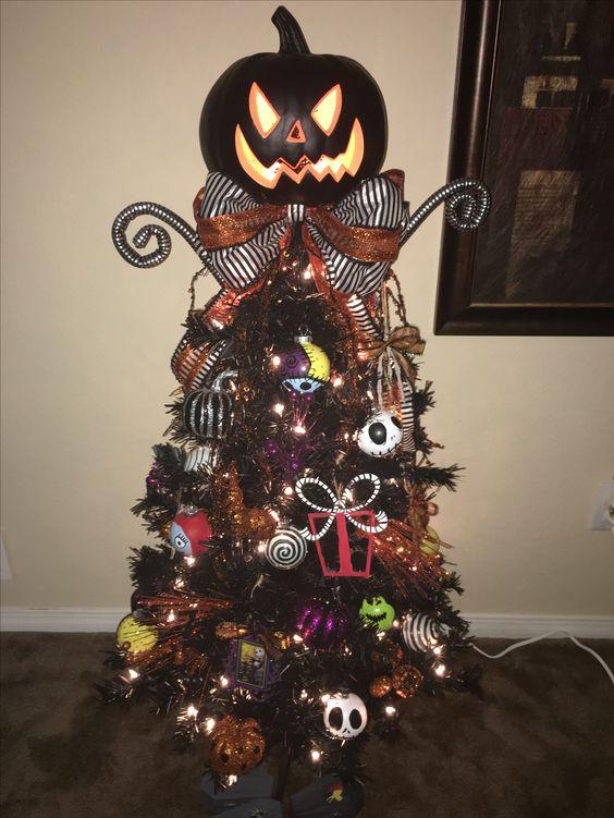 un arbre d'Halloween ou de Noël noir décoré d'ornements Nightmare Before Christmas, de lumières, d'un arc et d'une citrouille géante