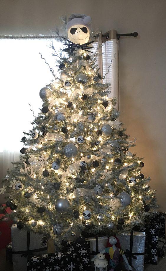 un sapin de Noël argenté illuminé avec des ornements argentés, noirs et blancs, des cloches et une tête de Jack Skellington sur le dessus