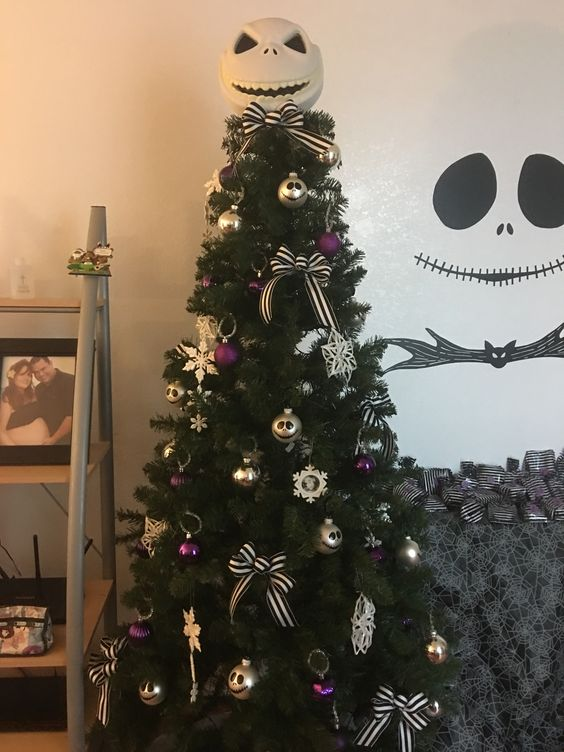 un sapin de Noël avec des ornements et des nœuds violets et dorés ainsi que des décorations Jack Skellington pour plus de chic