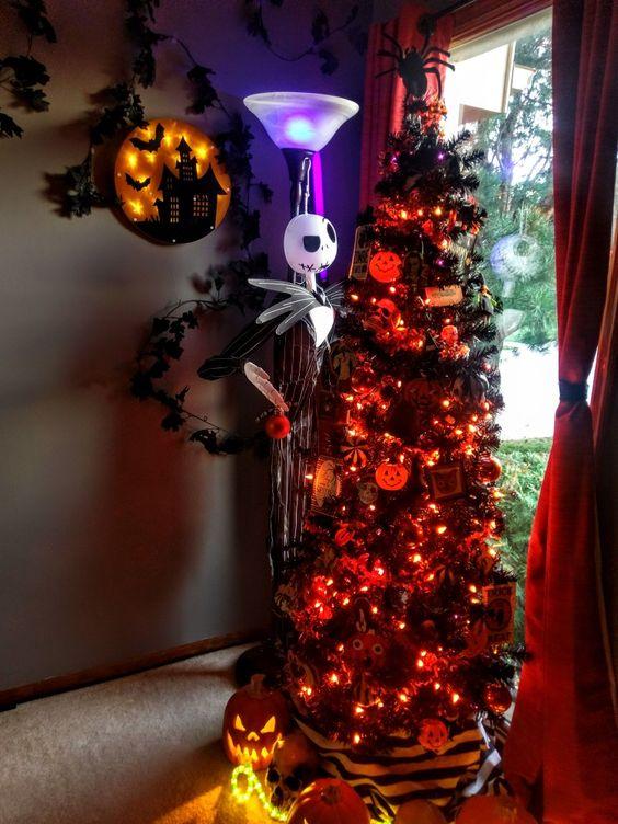un magnifique sapin de Noël noir avec des lumières oranges, des citrouilles, des ornements Nightmare Before Christmas et une figurine Jack Skellington à côté