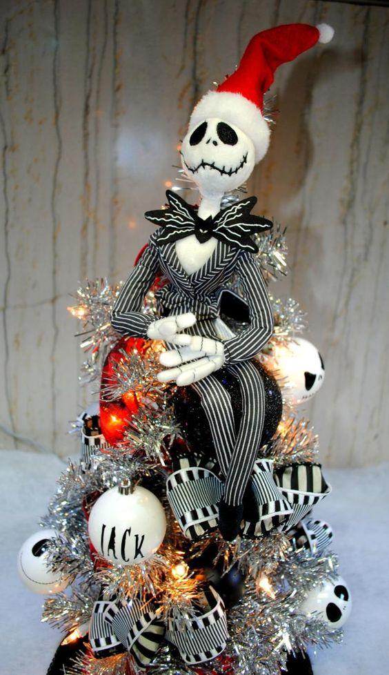 un arbre de Noël illuminé en argent Nightmare Before avec des ornements Jack et des rubans rayés est une idée charmante et audacieuse à bercer