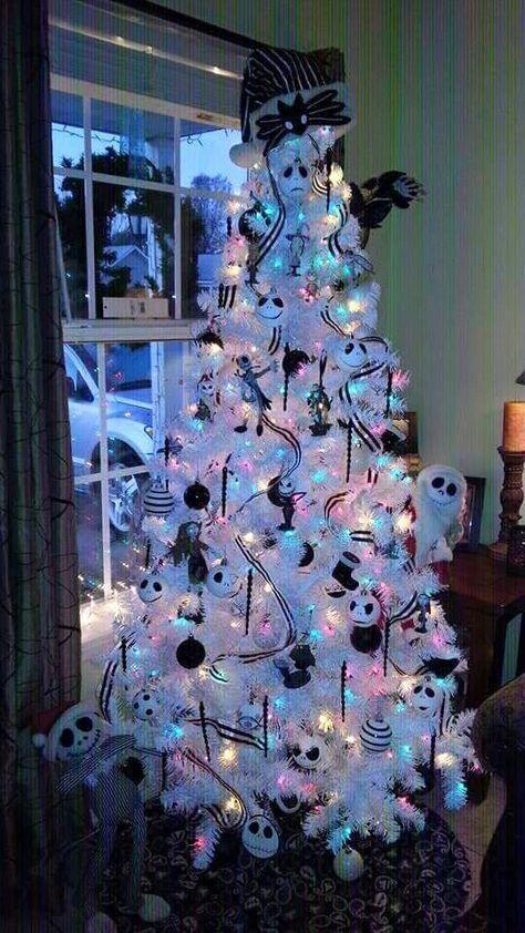 un sapin de Noël blanc avec des lumières colorées, des rubans et des ornements noirs et blancs, ceux de Jack Skellington, des arcs et des guirlandes