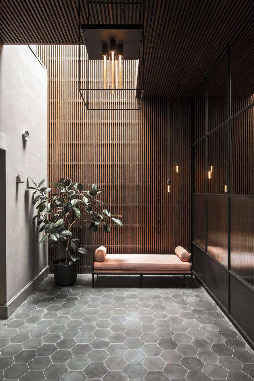 L'entrée comprend des carreaux hexagonaux gris, un canapé rose, une plante en pot, un puits de lumière et une lampe industrielle
