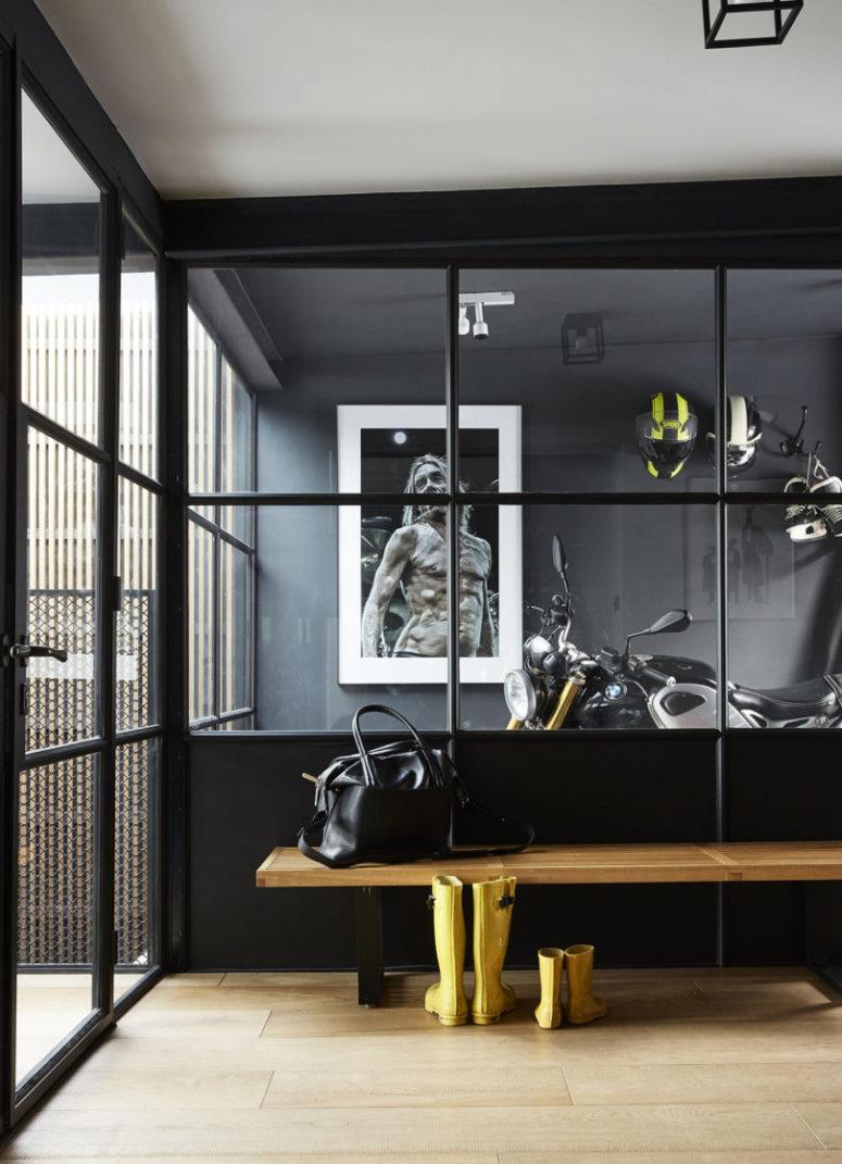 Des œuvres d'art remarquables, un grand miroir qui remplit l'espace de lumière naturelle, un banc en bois et une porte en verre rendent ce coin cool
