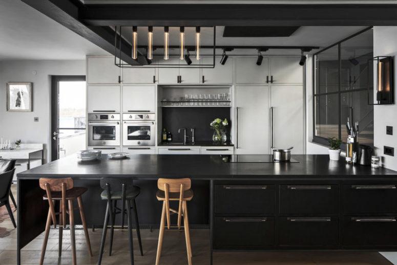 La cuisine est en noir et blanc, avec des armoires en contreplaqué et en métal, avec une lampe accrocheuse et de hauts tabourets