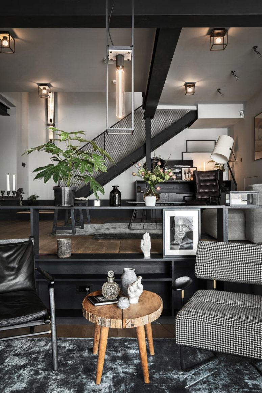 L'espace principal est un aménagement ouvert avec un salon, une cuisine et un espace salle à manger fait dans une palette de couleurs monochromes