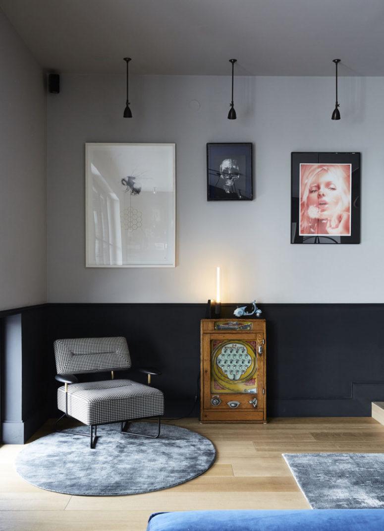 Ce coin comprend un mur de galerie unique, des lampes suspendues, une petite table d'appoint et une chaise chic et moderne du milieu du siècle