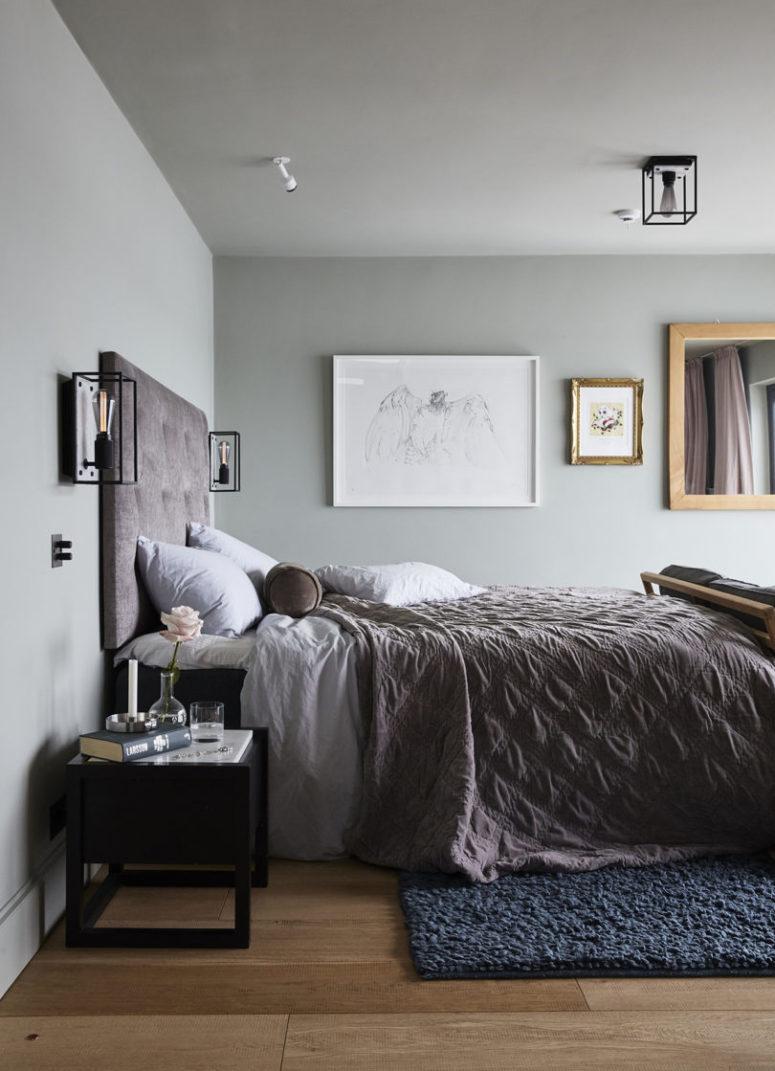 La chambre principale est très apaisante, avec des murs gris, un mur de galerie, des textiles rose poussiéreux et des touches de noir