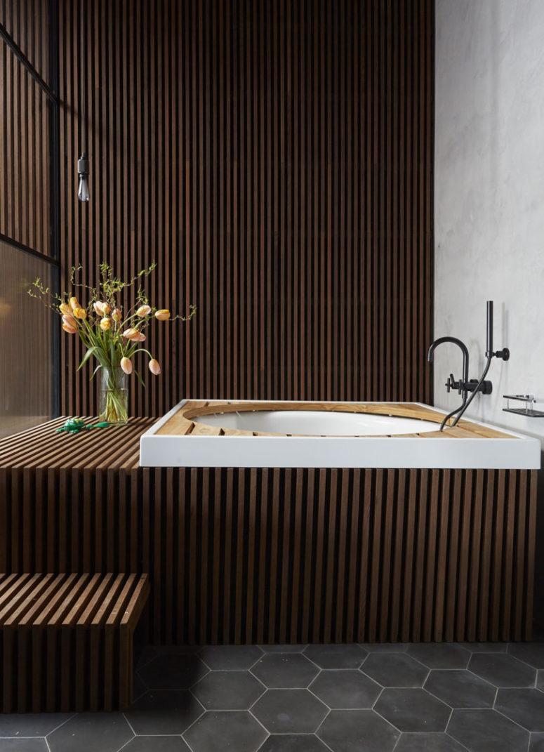 La salle de bain est faite de dalles en bois et d'une baignoire intégrée