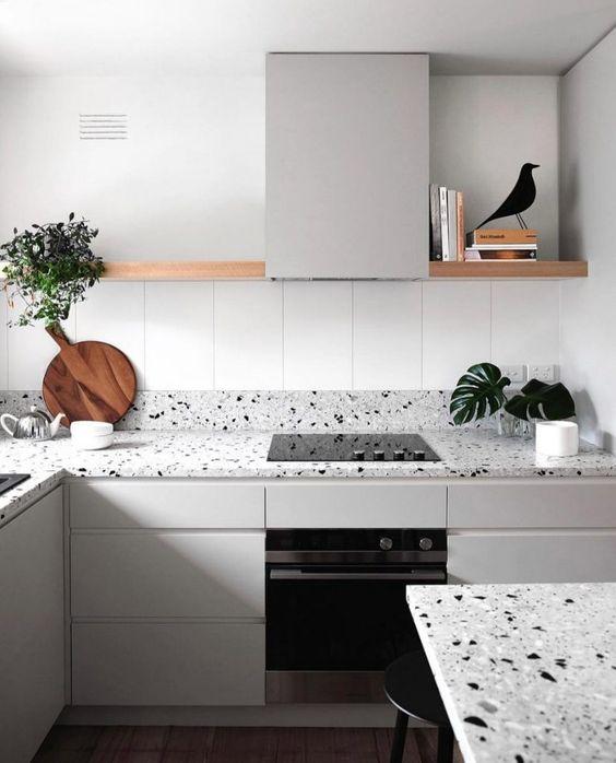 une cuisine minimaliste en gris tourterelle rehaussée d'un comptoir et d'un dosseret en terrazzo gris et d'une table assortie ici