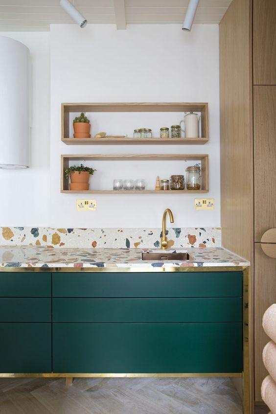 les armoires de cuisine vert chasseur rehaussées de touches dorées et de comptoirs en terrazzo brillant sont très chics et audacieux