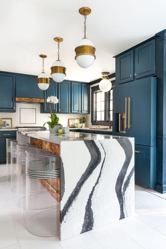 une cuisine bleue chic et un îlot de cuisine avec un magnifique comptoir en cascade de marbre blanc qui fait une déclaration ici