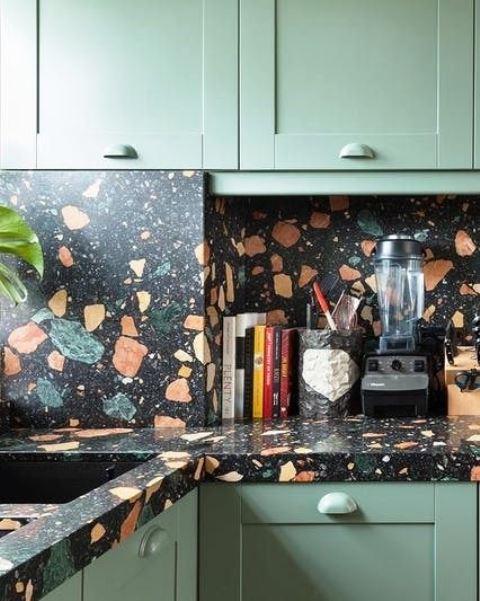 armoires de cuisine vert clair et un comptoir et un dosseret en terrazzo foncé pour donner à la cuisine un aspect exceptionnel