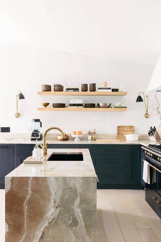 une cuisine en bois noir soulignée de plans de travail en marbre de couleur terre, dont une cascade qui fait une véritable déclaration