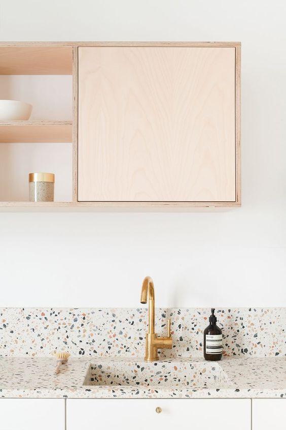 une cuisine éthérée et neutre avec des armoires de couleur claire et un comptoir et un dosseret en terrazzo clair ainsi que des touches d'or