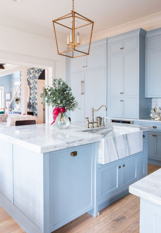 une belle et élégante cuisine bleu clair avec des comptoirs en marbre blanc qui font une déclaration luxueuse accentuant les couleurs