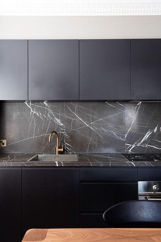 une cuisine minimaliste bleu nuit avec un dosseret et un plan de travail en marbre noir qui lui confèrent un aspect et une sensation de luxe ultimes