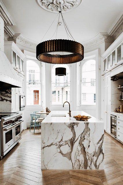 une luxueuse cuisine blanche avec un grand îlot de cuisine et un fantastique comptoir en marbre blanc qui impressionne à la fois
