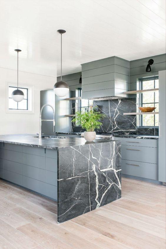 une cuisine en bois gris avec un dosseret en marbre noir et un îlot assorti avec un comptoir en cascade