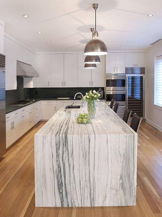 une cuisine monochrome avec un magnifique îlot de cuisine qui dispose d'un comptoir en marbre blanc et fait une déclaration