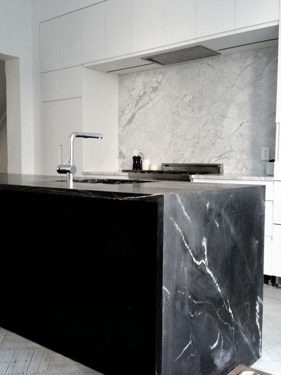 une cuisine blanche minimaliste et un îlot de cuisine noir avec un comptoir en marbre noir cool qui fait écho à un dosseret en marbre blanc
