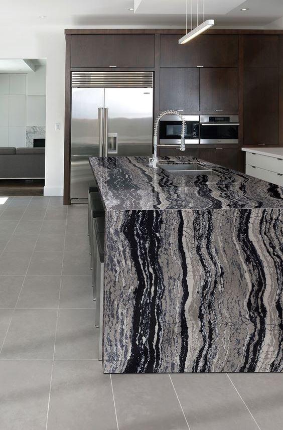 une cuisine sombre avec un îlot de cuisine accrocheur et un comptoir en pierre de cascade audacieux ainsi que des appareils en acier inoxydable pour une sensation moderne