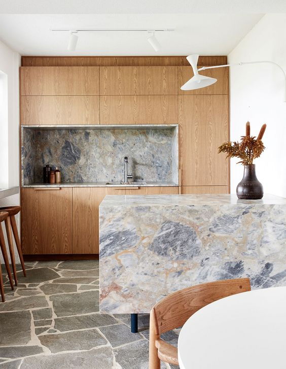 une petite cuisine de couleur claire avec un dosseret en marbre gris et des plans de travail dont un en cascade qui bascule
