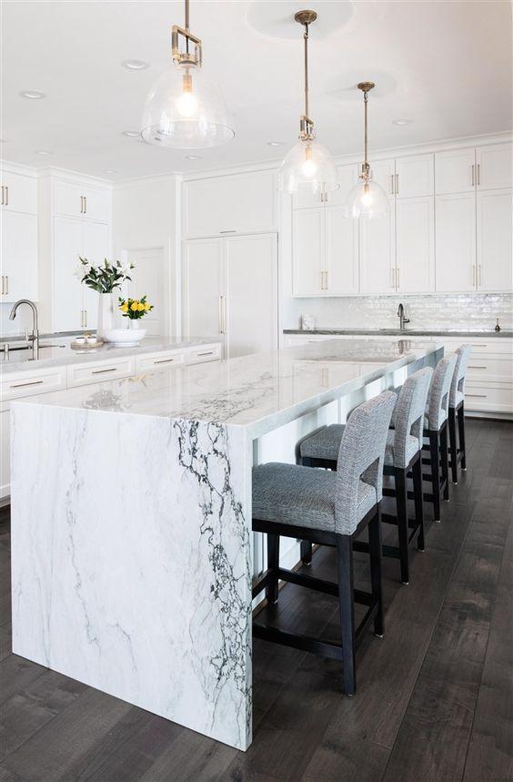 une élégante cuisine blanche avec un îlot de cuisine chic avec un comptoir en cascade de marbre blanc qui apporte du luxe ici
