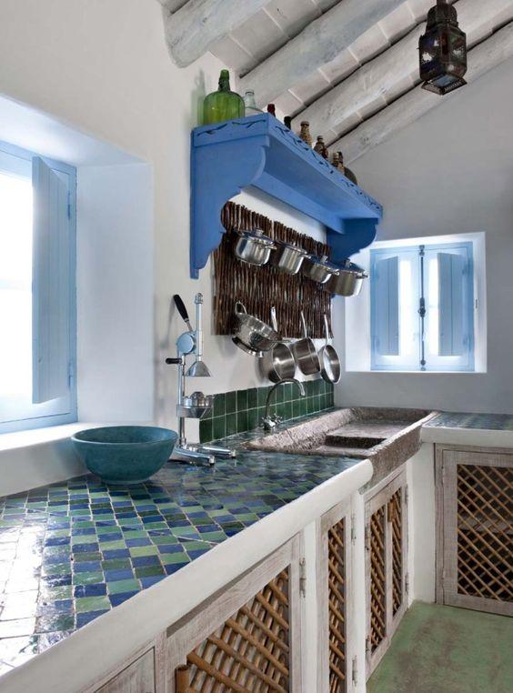 une cuisine neutre en bois de couleur claire, avec un évier en pierre et un plan de travail en carrelage brillant, ainsi qu'un dosseret en carrelage vert pour impressionner