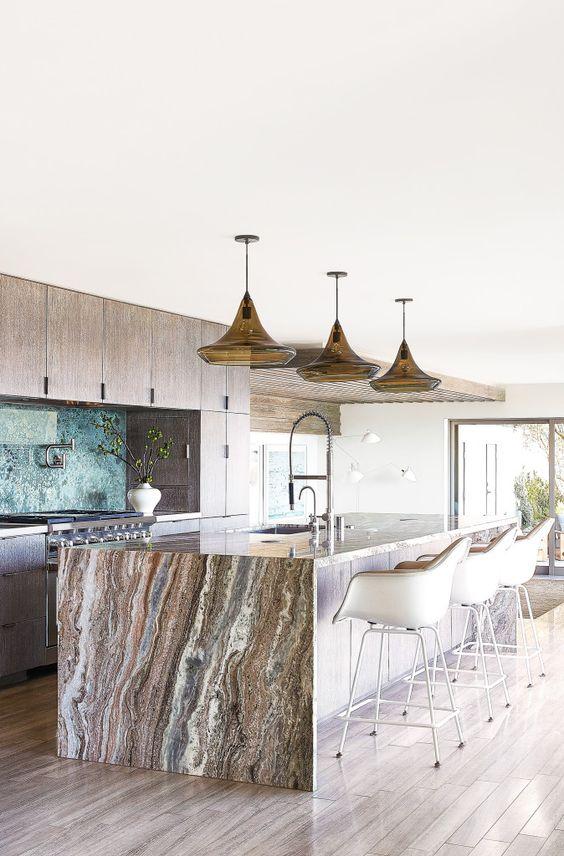 une cuisine en bois neutre avec un grand îlot de cuisine surmonté d'un magnifique plan de travail en pierre qui apporte une touche luxueuse
