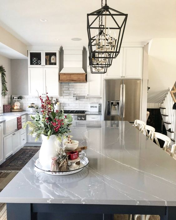 une cuisine traditionnelle neutre avec un comptoir en marbre gris, des suspensions noires et un dosseret en carreaux de métro blancs