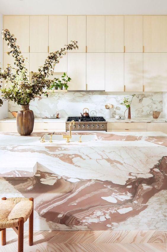 une cuisine élégante en contreplaqué avec un dosseret en marbre rose et un magnifique îlot de cuisine en marbre rose qui impressionne
