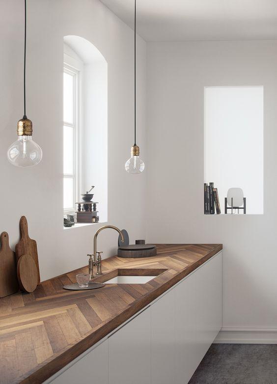 armoires de cuisine blanches élégantes avec un comptoir de cuisine en bois chevron richement teinté qui apporte de la couleur et de la texture