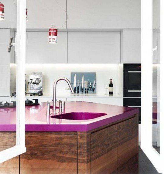 une cuisine blanche minimaliste et élégante et un îlot de cuisine teinté sombre avec un comptoir fuchsia qui fait une déclaration audacieuse ici