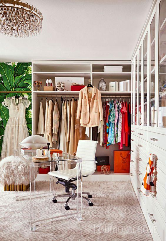 un bureau glam coloré avec un lustre en cristal, un tapis imprimé, un placard de fortune, un grand meuble de rangement fermé, un bureau en acrylique et une chaise blanche