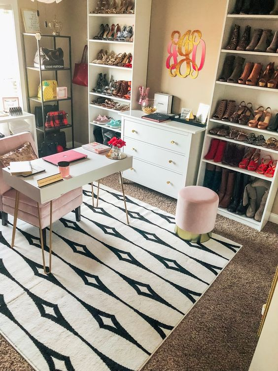 un bureau à domicile glam audacieux avec des tapis superposés, un petit bureau, une chaise et un pouf roses, des supports à chaussures et à sacs