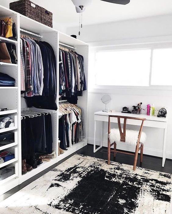un bureau chic monochromatique avec un bureau blanc, une chaise en bois, un placard de fortune et un tapis graphique