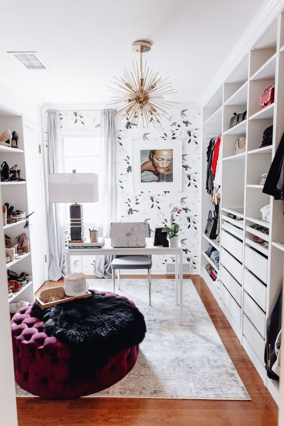 un petit bureau chic avec un grand meuble à chaussures, un bureau blanc et une chaise grise, un pouf violet et du papier peint botanique