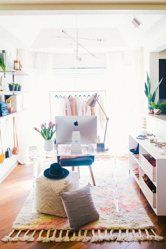 un cloffice coloré avec un placard de fortune, des étagères ouvertes et des unités de rangement, un bureau en acrylique, de nombreuses plantes en pot et des textiles colorés