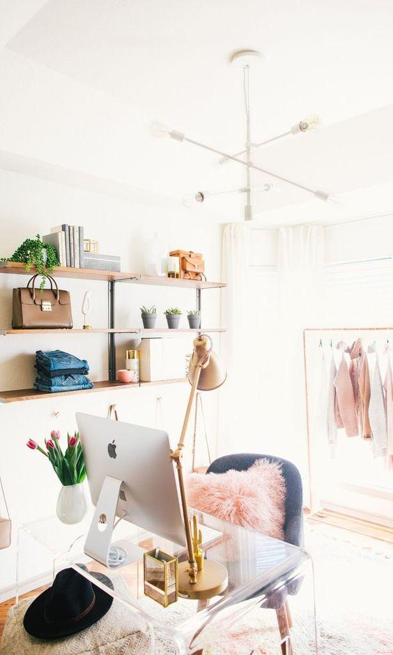 un cloffice mignon et glam avec des étagères ouvertes, un placard de fortune, un lustre blanc, un bureau en acrylique, une chaise grise et des touches de rose