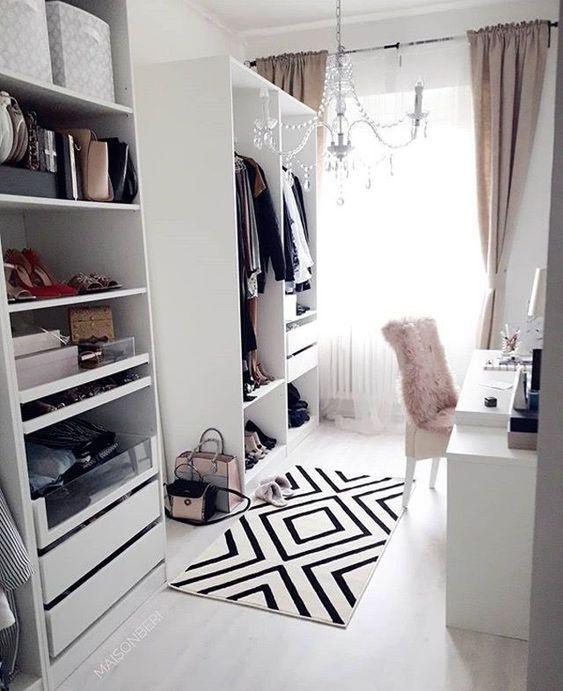 un joli bureau blanc avec un placard de fortune, un bureau blanc, une chaise en fourrure rose, un lustre en cristal, des rideaux rose clair et un tapis graphique