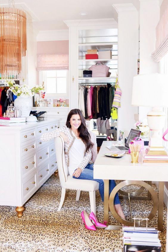 un bureau à domicile glam fou avec un lustre tendance, un tapis à imprimé léopard, un bureau accrocheur et audacieux, des étagères ouvertes et une commode
