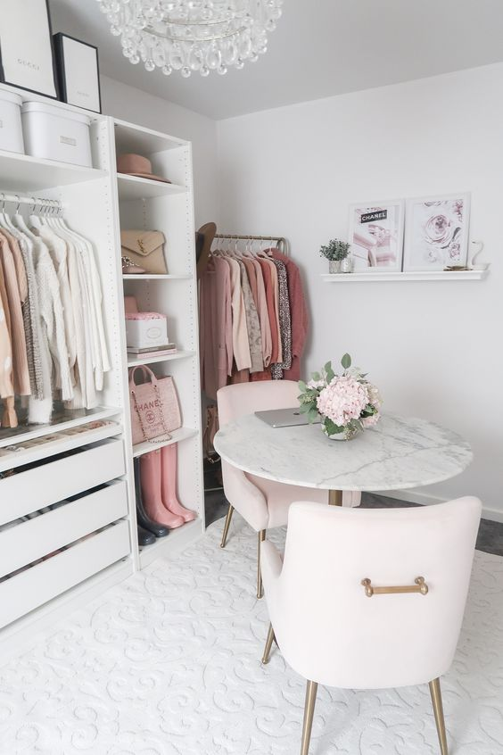 un cloffice romantique avec un placard de fortune blanc, un lustre en cristal, des œuvres d'art, des chaises blush et une table en marbre