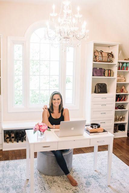 un petit et mignon bureau avec un bureau blanc, un pouf gris, des armoires blanches vintage, un lustre en cristal