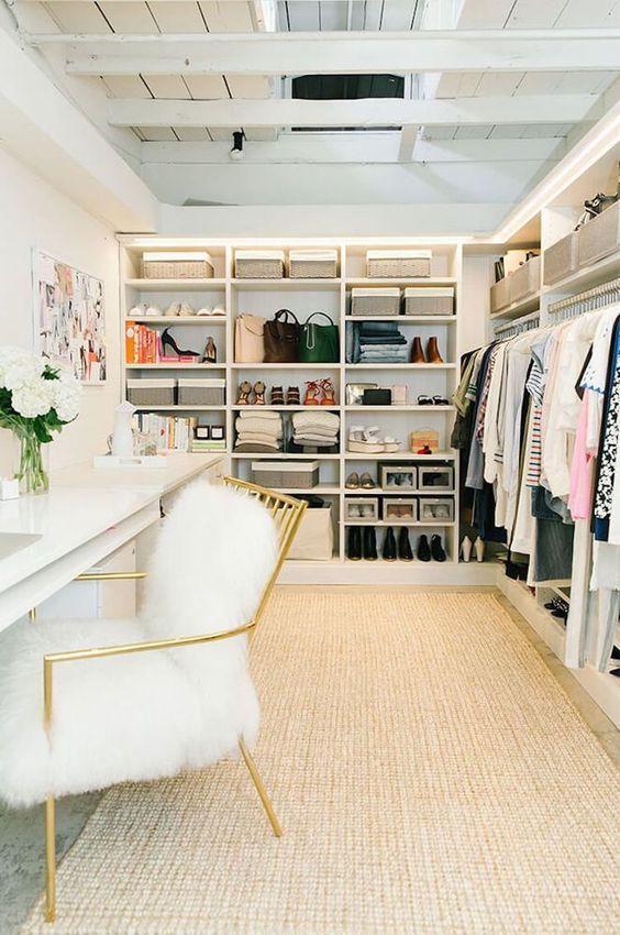 un cloffice glam avec un tapis neutre, un grand placard ouvert, un double bureau blanc, une chaise en fourrure or et blanc