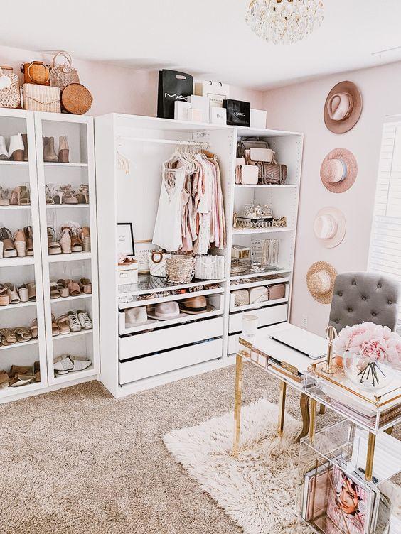 un bureau de fille avec un placard blanc de fortune, des chapeaux au mur, un lustre en cristal, un bureau acrylique accrocheur et un meuble de rangement