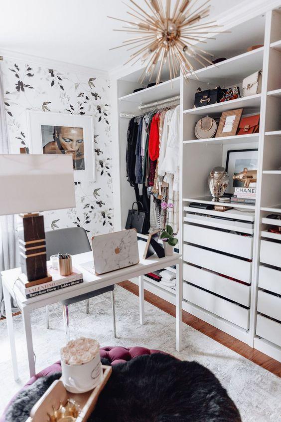 un petit bureau glam avec du papier peint botanique, un lustre sunburst, un simple bureau blanc et un placard ouvert qui prend tout un mur