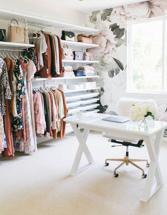 un bureau à domicile aéré et féminin avec un mur de papier peint à fleurs, un vaste placard de fortune avec des étagères ouvertes, un bureau à tréteaux et une chaise en fourrure blanche