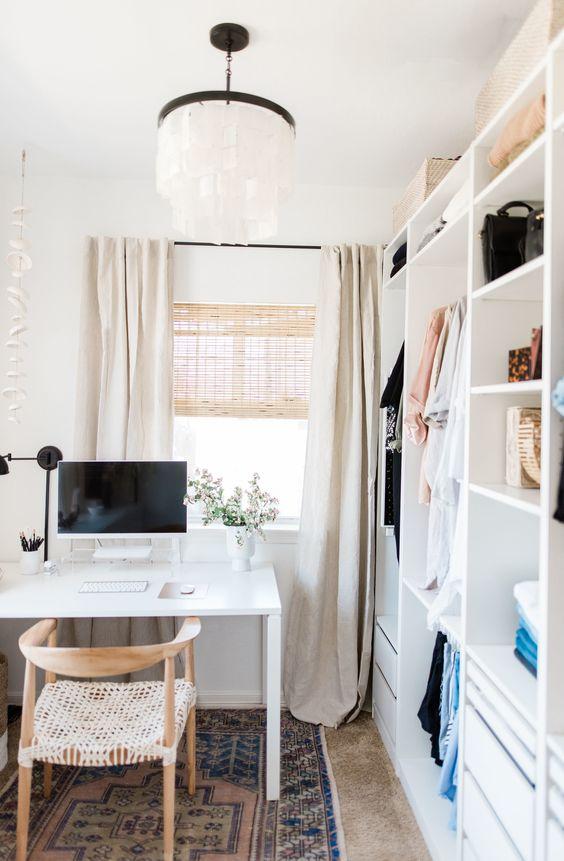 un petit bureau neutre avec un placard de fortune blanc, un bureau blanc et une chaise tressée, une lampe en papier et un tapis imprimé