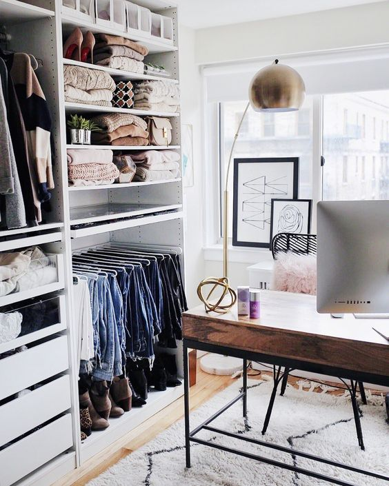 un petit bureau glam avec un grand placard de fortune, un bureau élégant en bois et métal, des œuvres d'art et une lampe en laiton accrocheuse